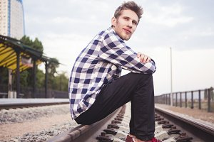 young man in casual clothes sitting on a railroad track