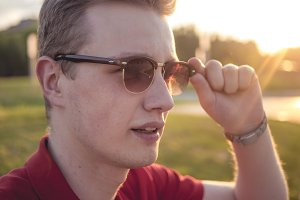 handsome young man portrait adjusting sunglasses on a sunny day