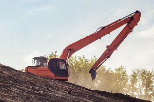 panorama of excavator digging ground with bucket with trees and sky on background