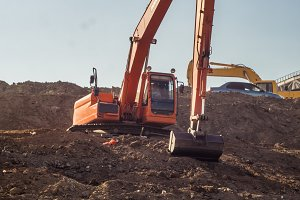 excavator with bucket making earth embankments and digging dusty ground