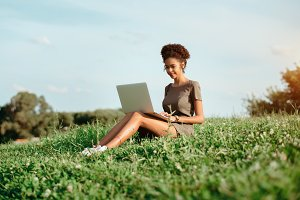 Black girl with laptop outdoors