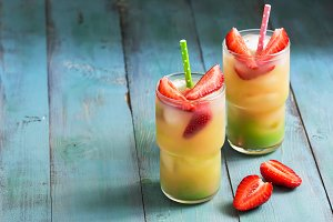 A colorful drink with strawberries on a blue rustic table. Copy space.
