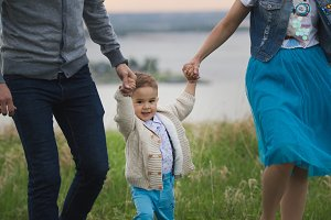 Young couple with a child dancing and having fun in nature - in front of river