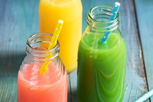 Pink, yellow and green drink bottled. Colorful juices. Summer drinks.