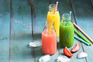Colorful drinks in bottles . Pink, yellow and green drink on a blue wooden table. Copy space