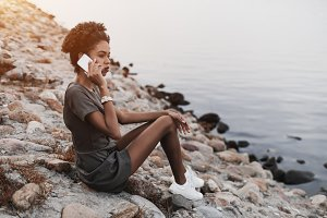 Black girl is phoning near river