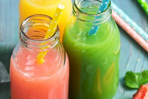 Colorful drinks in bottles . Pink, yellow and green drink on a blue wooden table