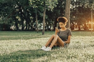 Afro girl on grass with cellphone
