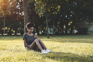 Afro girl on grass with smartphone