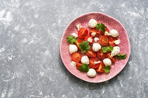 Mozzarella salad with tomatoes on a gray background. Top view, space for text.