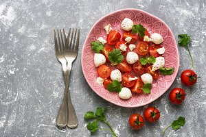 Mozzarella and cherry tomatoes are served on a pink plate. Gray background, top view.