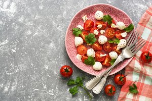 Fresh salad with mozzarella and tomatoes on a grey background, checkered napkin and forks.Copy space