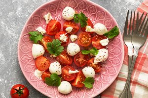 Salad with mozzarella and tomatoes on a gray background, checkered napkin and fork.Copy space, flat lay.
