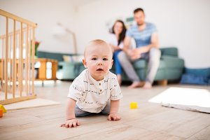A baby boy crawling on the floor at home, parents in the background.