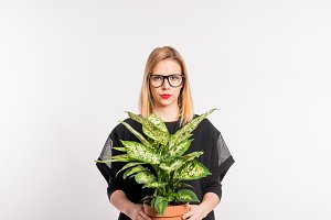 Young beautiful woman with black clothes in studio on white background, holding a plant.