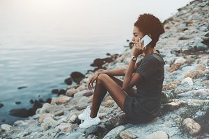 Afro girl phoning near the river