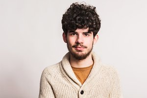 Portrait of a young man in woollen cardigan in a studio. Copy space.