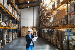 Senior woman warehouse manager or supervisor with tablet and smartphone, making a phone call.