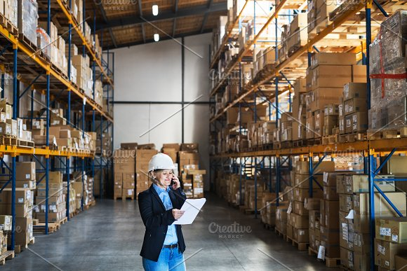 Senior Woman Warehouse Manager Or Supervisor With Tablet And Smartphone Making A Phone Call