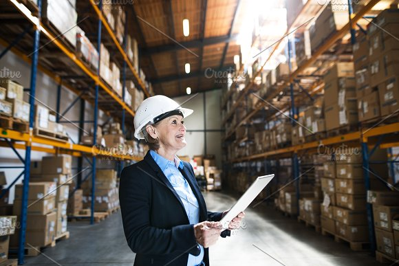 Senior Woman Warehouse Manager Or Supervisor With Tablet Working