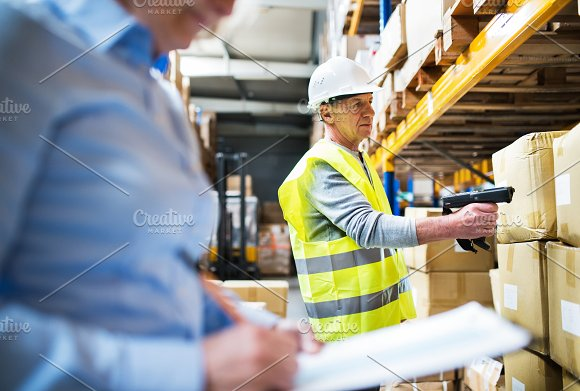 Senior Woman Manager And Man Worker Working In A Warehouse