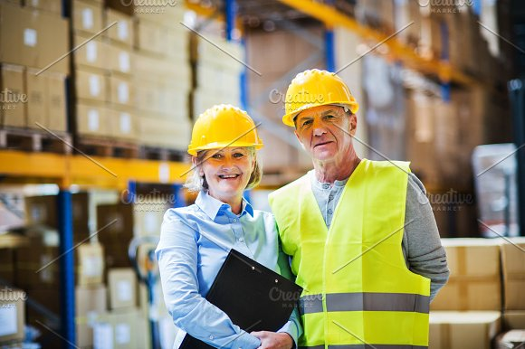Senior Woman Manager And Man Worker Standing In A Warehouse