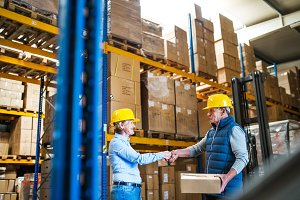 Senior woman managers or workers working in a warehouse, shaking hands.