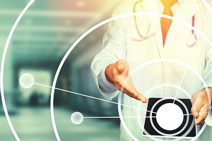 Unrecognizable male doctor in a white lab coat with a stethoscope uses a tablet, using a digital patient support system, test results and data registration