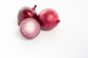 Red onion in a cut. A pile of onions on a white background.