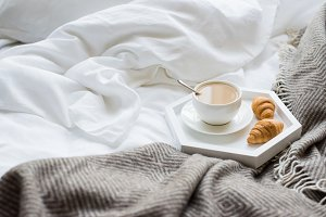 Cozy breakfast in bed, cup of coffee