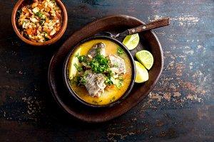 CHILEAN FOOD. Fish soup CALDILLO DE CONGRIO served in clay bowl, top view
