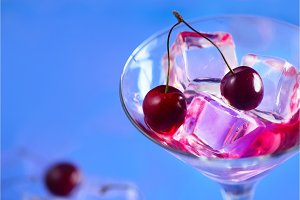 Cherry cocktail close-up. Martini glass with ice cubes and cherries on a bright blue background with copy space. Hot summer day refreshment concept