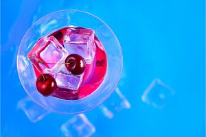 Cherry liquor cocktail glass from above on a blue background. Refreshing cold drink flat lay with copy space
