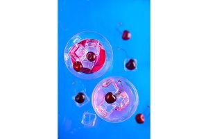 Cherry cider cocktail glasses from above on a blue background. Refreshing cold drink flat lay with copy space