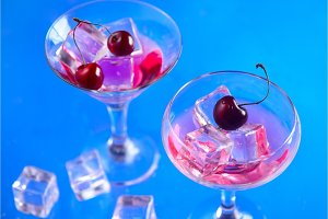 Cherry drink in cocktail glasses with ice cubes on a blue background. Refreshing cold drink with copy space. Summer beverage concept