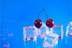 Fresh cherries on a stack of ice cubes close-up on a bright blue background. Refreshing summer beverage concept with copy space