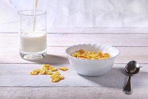 Corn Flakes cereal in a bowl and glass with milk. Morning breakfast.