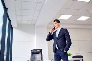 Brunet businessman talking on the phone in a business office
