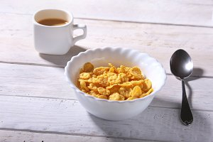 Corn Flakes cereal with milk in a bowl and cap with espresso coffee. Morning breakfast.