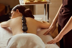 Massage stones on  back of a woman at the spa salon
