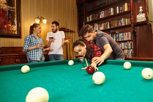 Young men and women playing billiards at office after work.