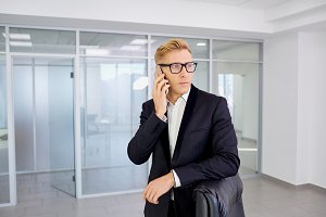 Businessman blonde in glasses talking on mobile, laughing smilin