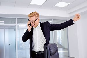 The concept of success, victory, business. Businessman blonde with glasses raised his fist up, talking on phone smiling, laughing