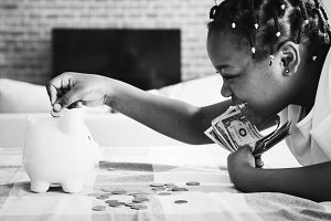 girl collecting money in piggy bank