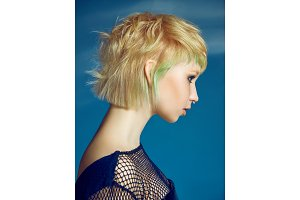 Close-up indoor portrait of lovely girl with blonde hair. Studio shot of graceful young woman with short haircut