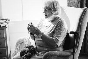 Senior woman knitting at home