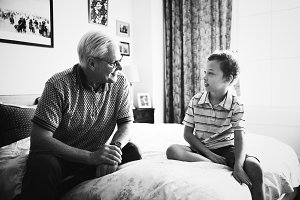 Grandpa and grandson sitting on bed