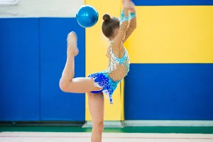 Beautiful little active gymnast girl with her performance on the carpet
