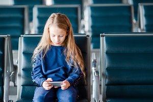 Adorable little girl in airport near big window indoor