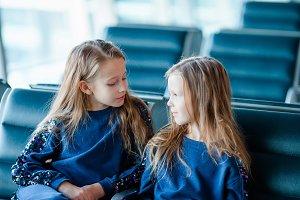 Little adorable girls in airport near big window